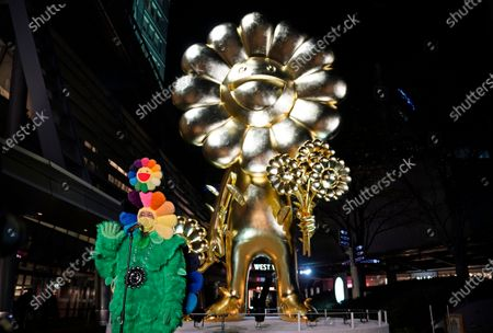 Japanese contemporary artist Takashi Murakami speaks to media before his artwork 'Flower Parent and Child' at Roppongi Hills 66 Plaza in Tokyo, Japan, 26 November 2020. Weighing over 11 tons, the 10 meters high golden 'Flower Parent and Child' sculpture is one of Murakami's largest artworks.