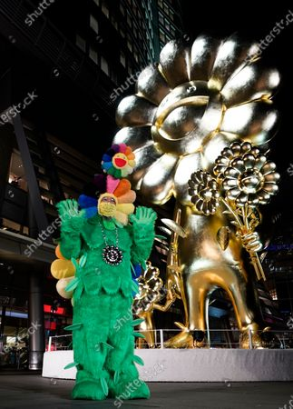 Japanese contemporary artist Takashi Murakami poses before his artwork 'Flower Parent and Child' at Roppongi Hills 66 Plaza in Tokyo, Japan, 26 November 2020. Weighing over 11 tons, the 10 meters high golden 'Flower Parent and Child' sculpture is one of Murakami's largest artworks.