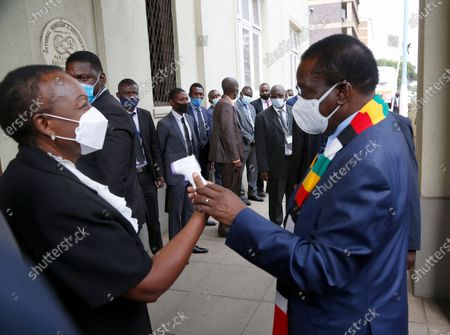 Stock Picture of Zimbabwean President Emmerson Mnangagwa (R) checks the display of a thermometer after his temperature has been taken upon his arrival at the House of Parliament, in Harare, Zimbabwe, 26 November 2020. Mnangagwa attended the presentation of the 2021 national budget by the Minister of Finance and Economic Development, Professor Mthuli Ncube (not in the picture).