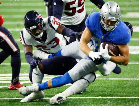 Detroit Lions tight end T.J. Hockenson (88) is tackled by Houston Texans linebacker Tyrell Adams (50) and linebacker Jonathan Greenard (52) during an NFL football game, in Detroit