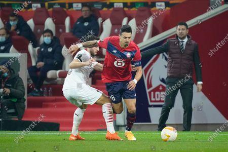 Jose Fonte of Lille is challenged by Hakan Calhanoglu of Milan as Milan coach Daniele Bonera looks on