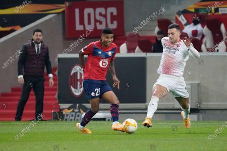 Reinildo Mandava of Lille takes on Diogo Dalot of Milan as Milan coach Daniele Bonera looks on
