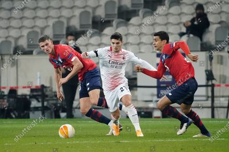 Brahim Diaz of Milan tries to slip between Sven Botman of Lille (left) and Benjamin Andre of Lille (right)