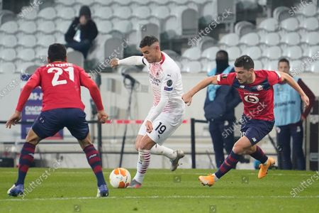 Theo Hernandez of Milan takes on Jeremy Pied of Lille (right) and Benjamin Andre of Lille (left)