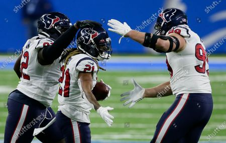 Houston Texans cornerback Bradley Roby (21) celebrates with Houston Texans nose tackle Brandon Dunn, left, and defensive end J.J. Watt, right, after recovering a Detroit Lions fumble during the first half of an NFL football game, in Detroit