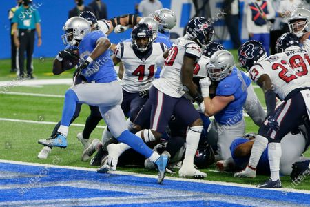 Detroit Lions running back Adrian Peterson breaks through the Houston Texans defense for a 1-yard touchdown run during the first half of an NFL football game, in Detroit