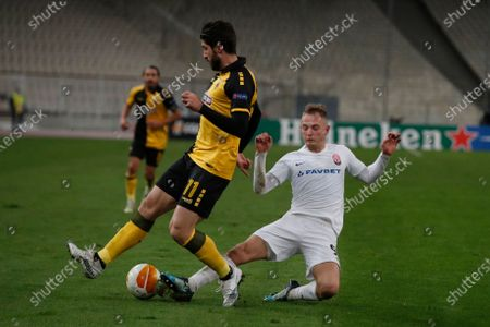 AEK's Karim Ansarifard, left, is tackled by Zorya Luhansk's Andrejs Ciganiks during the Europa League group G soccer match between AEK Athens and Zorya Luhansk at the Olympic stadium in Athens