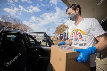 Jon Ossoff, Democratic candidate for senate in Georgia, and his wife Dr. Alisha Kramer help Hosea Helps volunteers give out food packages and items to those in need on Thanksgiving at the Georgia World Congress Center