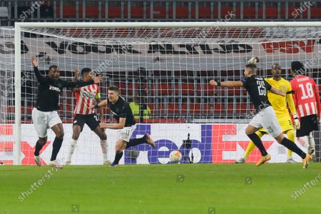 Stock Image of Shot by PAOK's Christos Tzolis, third left, bounced off PAOK's Fernando Varela, left, who scored his side's first goal during the Group E Europa League soccer match between PSV and PAOK at the Philips stadium in Eindhoven, Netherlands