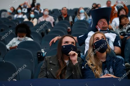 Stock Photo of Fans watch a pre-recorded musical performance by Kane Brown on the video board at halftime of an NFL football game between the Washington Football Team and Dallas Cowboys in Arlington, Texas