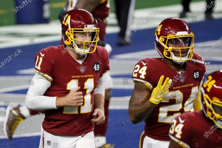 Washington Football Team's Alex Smith (11) and Antonio Gibson (24) jog to the sideline after Gibson ran the ball for a touchdown in the second half of an NFL football game against the Dallas Cowboys in Arlington, Texas, . Gibson, who is gesturing three with his right hand, scored three touchdowns in the game against the Cowboys