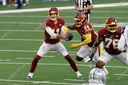Washington Football Team quarterback Alex Smith (11) hands the ball off to running back Antonio Gibson (24) during the first half of an NFL football game against the Dallas Cowboys in Arlington, Texas