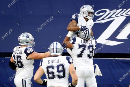 Dallas Cowboys' Connor McGovern (66), Brandon Knight (69) and Joe Looney (73) celebrate with Amari Cooper after his touchdown catch in the first half of an NFL football game against the Washington Football Team in Arlington, Texas