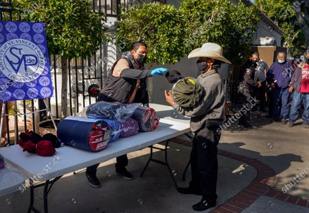 Stock Image of Volunteers with Society of St. Vincent de Paul Los Angeles distribute meals and sleeping bags at Our Lady of Guadalupe in Los Angeles on Thanksgiving Day