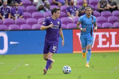 Orlando City midfielder Mauricio Pereyra (10) controls the ball in front of New York City FC defender Ronald Matarrita (22) during overtime of an MLS soccer playoff match, in Orlando, Fla