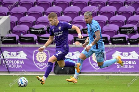 Orlando City forward Chris Mueller (9) controls a ball in front of New York City FC defender Ronald Matarrita (22) during the second half of an MLS soccer playoff match, in Orlando, Fla