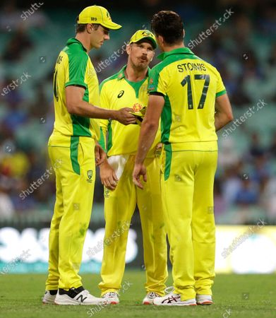 Australian captain Aaron Finch, centre, talks to bowlers Pat Cummins, left, and Marcus Stoinis during the one day international cricket match between India and Australia at the Sydney Cricket Ground in Sydney, Australia