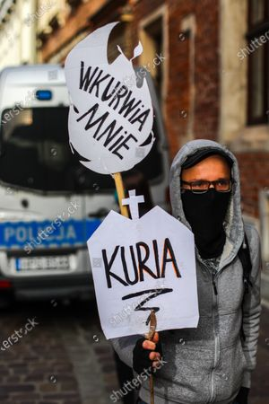 A protester wearing a face mask holds a placard during the demonstration. Activists protested on Kanoniczna Street in Cracow. The protest was an aftermath of a recently released reportage 'Don Stanislao. The second face of cardinal Dziwisz' that indicated that cardinal Dziwisz, long-time aide of pope John Paul II, could be responsible for covering up cases of pedophilia among catholic priests. People gathered on the street demanding explanations from the church and expressed support for the victims of pedophilia.