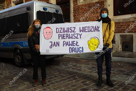 Protesters wearing face masks hold a banner that says Dziwisz knew first, John Paul second during the demonstration. Activists protested on Kanoniczna Street in Cracow. The protest was an aftermath of a recently released reportage 'Don Stanislao. The second face of cardinal Dziwisz' that indicated that cardinal Dziwisz, long-time aide of pope John Paul II, could be responsible for covering up cases of pedophilia among catholic priests. People gathered on the street demanding explanations from the church and expressed support for the victims of pedophilia.