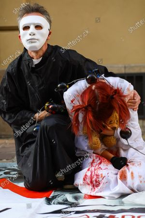 Stock Picture of Protesters wearing white masks covered with fake blood symbolising the suffering of the victims take part during the demonstration. Activists protested on Kanoniczna Street in Cracow. The protest was an aftermath of a recently released reportage 'Don Stanislao. The second face of cardinal Dziwisz' that indicated that cardinal Dziwisz, long-time aide of pope John Paul II, could be responsible for covering up cases of pedophilia among catholic priests. People gathered on the street demanding explanations from the church and expressed support for the victims of pedophilia.