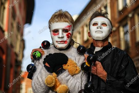 Stock Image of Protesters wearing white masks covered with fake blood symbolising the suffering of the victims take part during the demonstration. Activists protested on Kanoniczna Street in Cracow. The protest was an aftermath of a recently released reportage 'Don Stanislao. The second face of cardinal Dziwisz' that indicated that cardinal Dziwisz, long-time aide of pope John Paul II, could be responsible for covering up cases of pedophilia among catholic priests. People gathered on the street demanding explanations from the church and expressed support for the victims of pedophilia.