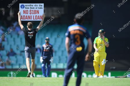 Aaron Finch (R) of Australia looks on as a pitch invader protesting against the Adani Coal Mine stands in the middle of the SCG during the first ODI cricket match between Australia and India at the SCG in Sydney, Australia, 27 November 2020.