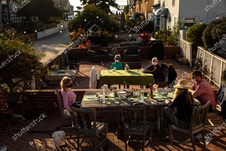 Grandmothers Ann Anderson, in green and G.G., in purple, had their own table, while celebrating with their children, Teri and Joe Anderson, right and grandchildren, including, Kelsey Anderson, left and Jenny and Emma, who were inside preparing dessert, following their Thanksgiving dinner outside, 17th Street, in Hermosa Beach, CA, Thursday, Nov. 26, 2020. (Jay L. Clendenin / Los Angeles Times)