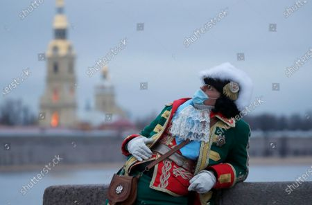 Street actor wearing protective face mask and costume of the Tsar Peter the Great poses to photographer with the Peter and Paul fortress on the background in St. Petersburg, Russia, 27 November 2020. In the past 24 hours, Russia registered 27, 543 new cases caused by the SARS-CoV-2 coronavirus infection and 496 coronavirus-related deaths.
