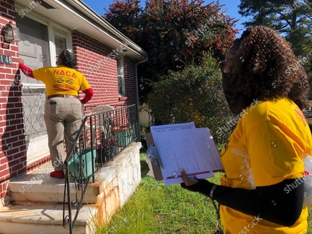 Phyllis Morrow knocks on a door in Decatur, Ga. on . Morrow and Jocelyn Johnson, foreground, are going door to door for the Neighborhood Assistance Corporation of America to encourage people to vote for Democrats Jon Ossoff and Raphael Warnock in Georgia's pivotal Jan. 5 runoff elections for U.S. Senate