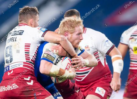 St Helens's James Graham is tackled by Wigan's Sam Powell.