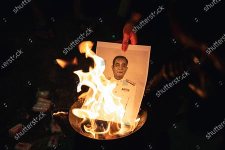 A protester burns a photo of a Thailand Prime Minister Prayuth Chan-ocha during the demonstration.
