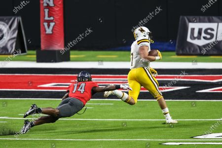Wyoming Cowboys running back Trey Smith (7) scores a touchdown while avoiding a diving UNLV Rebels defensive back Tyson Player (14) during the NCAA football game featuring the Wyoming Cowboys and the UNLV Rebels in Las Vegas, NV. The Wyoming Cowboys defeated the UNLV Rebels 45 to 14