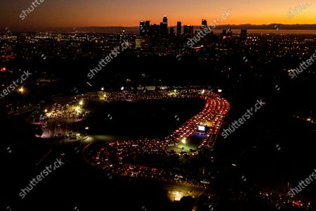 """In this Nov 18, 2020, file aerial photo, motorists wait in long lines to take a coronavirus test in a parking lot at Dodger Stadium in Los Angeles. The Los Angeles County has announced a new stay-home order as coronavirus cases surge out of control in the nation's most populous county. The three-3 week order take effect . The order advises residents to stay home """"as much as possible"""" and to wear a face covering when they go out. It bans people from gathering with people who aren't in their households, whether publicly or privately"""