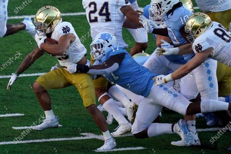 Notre Dame running back Kyren Williams runs while North Carolina linebacker Chris Collins (17) tries to tackle during the first half of an NCAA college football game in Chapel Hill, N.C