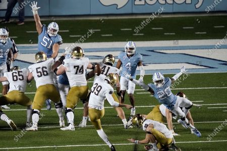 Notre Dame place kicker Jonathan Doerer (39) kicks while North Carolina defensive back Tony Grimes (20) rushes in during the second half of an NCAA college football game in Chapel Hill, N.C