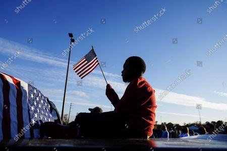 Xavier Watts, 9, waves an American flag during a camping rally for Georgia Democratic U.S. Senate candidates Jon Ossoff and Raphael Warnock in Marietta, Ga