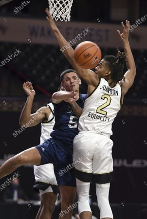 Longwood's Juan Munoz passes the ball as he drives to the basket under pressure from Wake Forest's Jalen Johnson during an NCAA basketball game, in Winston-Salem, N.C