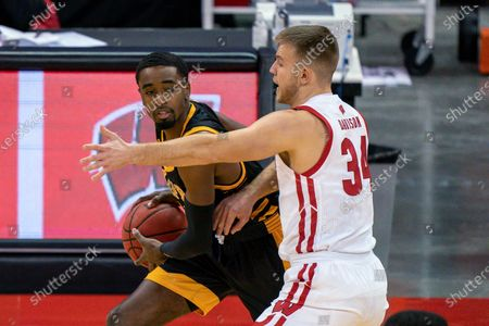 Arkansas-Pine Bluff's Shaun Doss (21) looks to get around Wisconsin's Brad Davison (34) during the first half of an NCAA college basketball game, in Madison, Wis