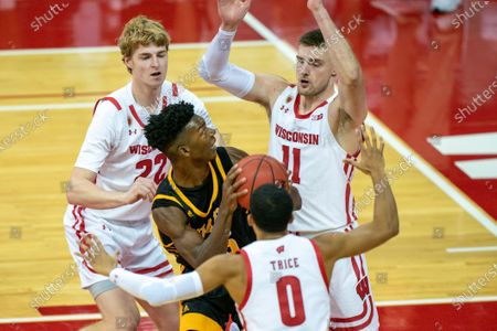Arkansas-Pine Bluff's Alvin Stredic, center, goes up against Wisconsin's Steven Crowl (22), D'Mitrik Trice (0) and Micah Potter (11) during the first half of an NCAA college basketball game, in Madison, Wis