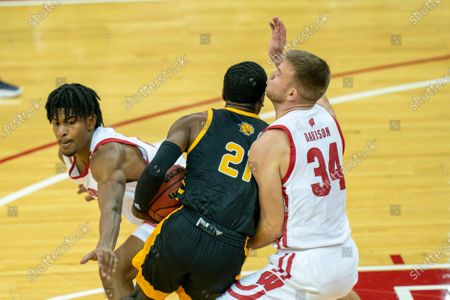 Arkansas-Pine Bluff's Shaun Doss (21) maneuvers between Wisconsin's Aleem Ford, left, and Brad Davison during the first half of an NCAA college basketball game, in Madison, Wis