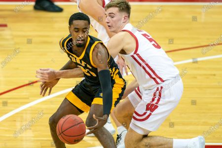 Wisconsin's Tyler Wahl (5) reaches in on Arkansas-Pine Bluff's Shaun Doss (21) during the first half of an NCAA college basketball game, in Madison, Wis