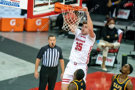 Wisconsin's Nate Reuvers (35) dunks over Arkansas-Pine Bluff's Markedric Bell (3) and Shaun Doss, right, during the first half of an NCAA college basketball game, in Madison, Wis