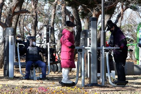 People wearing face masks as a precaution against the coronavirus exercise at a park in Goyang, South Korea, . South Korea has reported more than 500 new coronavirus cases for the third straight day, the speed of viral spread unseen since the worst wave of the outbreak in spring