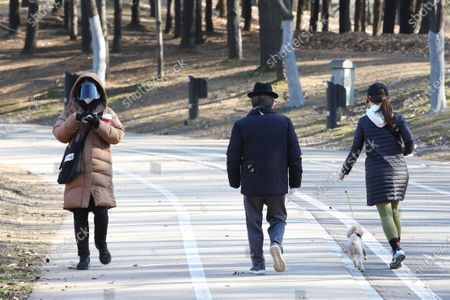 Woman wearing a face mask as a precaution against the coronavirus walks at a park in Goyang, South Korea, . South Korea has reported more than 500 new coronavirus cases for the third straight day, the speed of viral spread unseen since the worst wave of the outbreak in spring