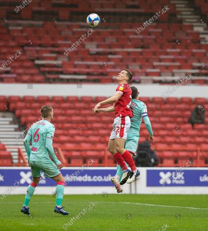 Ryan Yates of Nottingham Forest in the air gets above Matt Grimes of Swansea City AFC to head the ball; City Ground, Nottinghamshire, Midlands, England; English Football League Championship Football, Nottingham Forest versus Swansea City.