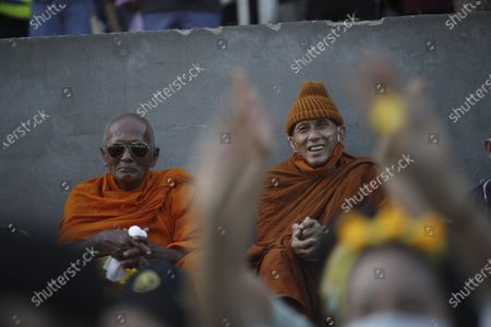 A Buddhist monk smiles as he sits behind Thai anti-government protesters flashing a three-finger salute during a street protest calling for political and monarchical reform in Bangkok, Thailand, 28 November 2020. Thailand has been facing political turmoil amid months-long street protests calling for the political and monarchical reform and the resignation of the prime minister Prayuth Chan-ocha.