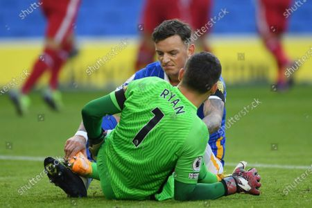 Brighton's Ben White, background and Brighton's goalkeeper Mathew Ryan lie on the pitch during the English Premier League soccer match between Brighton and Hove Albion and Liverpool at the Amex stadium in Brighton, England