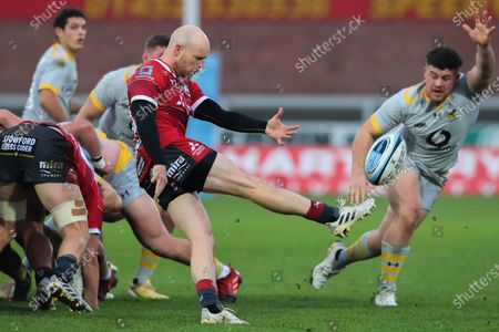 Joe Simpson of Gloucester Rugby box kicks, as Alfie Barbeary of Wasps attempts to charge down