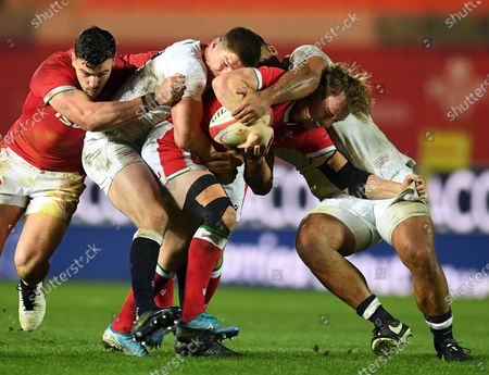 Nick Tompkins of Wales is tackled by Owen Farrell and Billy Vunipola of England.