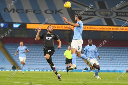 Stock Picture of Manchester City defender Rúben Dias (3) heads clear under pressure from Burnley forward Jay Rodriguez (19) during the Premier League match between Manchester City and Burnley at the Etihad Stadium, Manchester